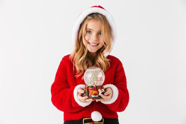 Vrolijk meisje dat geïsoleerde de zitting van het kerstmiskostuum draagt, een sneeuwbol houdt