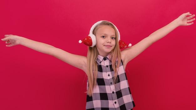 Vrolijk meisje dat haar vingers wijst. een kind in een warme oorwarmers op een rode achtergrond.