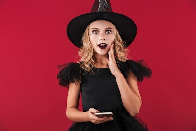 Vrolijk meisje dat halloween-heksenkostuum staand draagt