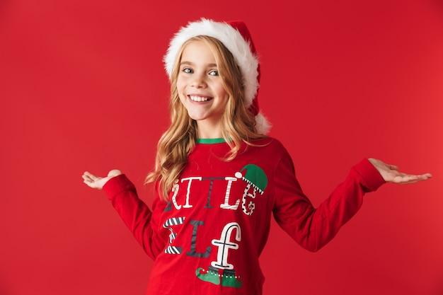 Vrolijk meisje dat kerstmishoed draagt die zich geïsoleerd bevindt, exemplaarruimte voorstelt