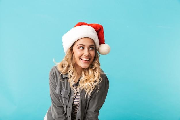 Vrolijk meisje dat kerstmishoed draagt die zich geïsoleerd over blauw bevindt