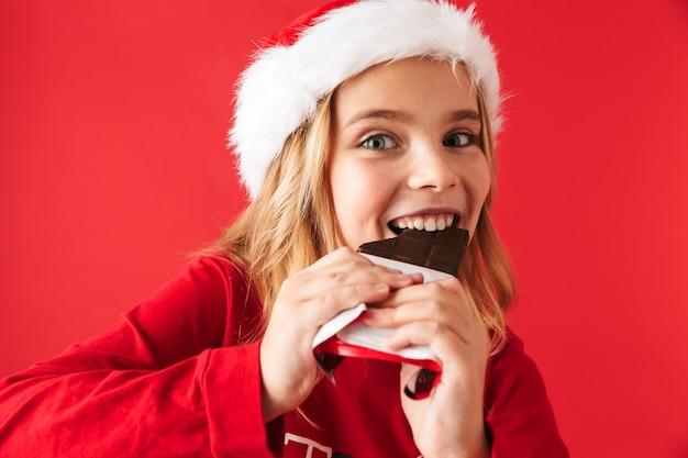 Vrolijk meisje dat kerstmiskostuum draagt dat zich geïsoleerd bevindt, chocolade eet