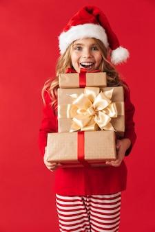 Vrolijk meisje dat kerstmiskostuum draagt dat zich geïsoleerd bevindt, die giftdozen houdt