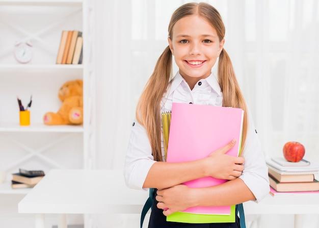 Vrolijk meisje dat met boeken glimlacht