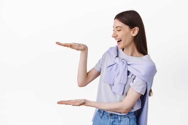 Vrolijk meisje dat naar lege ruimte kijkt, een grote objectdoos vasthoudt, lacht terwijl ze naar copyspace staart, over een witte muur staat