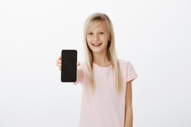 Vrolijk meisje dat nieuwe mobiele telefoon toont aan vrienden. gelukkig schattig kind met blond haar, hand met smartphone trekken
