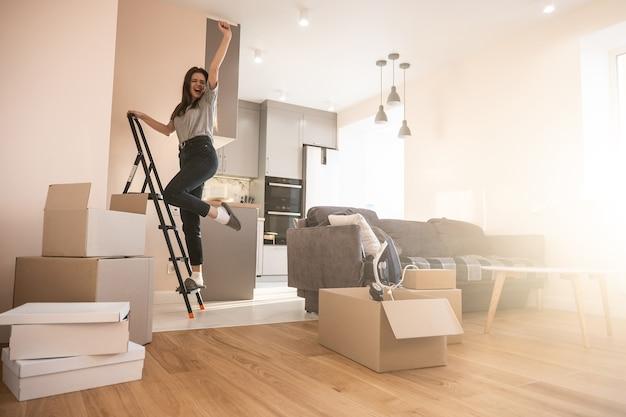 Vrolijk meisje dat op de ladder staat en thuis viert. jonge mooie europese vrouw. kartonnen dozen met dingen. concept van verhuizen in nieuwe flat. interieur van studio-appartement. zonnige dag