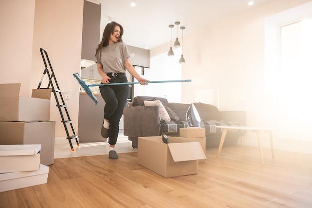 Vrolijk meisje dat thuis op dweil als gitaar speelt. jonge mooie europese vrouw. kartonnen dozen met dingen. concept van verhuizen in nieuwe flat. interieur van studio-appartement. zonnige dag