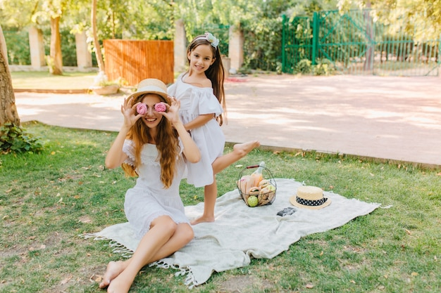 Vrolijk meisje dat zich op één been bevindt terwijl haar grappige moeder met koekjes voor de gek houdt. outdoor portret van een grapje langharige vrouw genieten van picknick met dochter in vakantie.