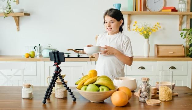 Vrolijk meisje deelt geheimen in de uitzending van een kookblogvideo