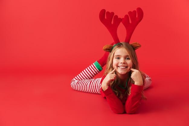 Vrolijk meisje die geïsoleerde het kostuumzitting van het kerstmisregendeer dragen