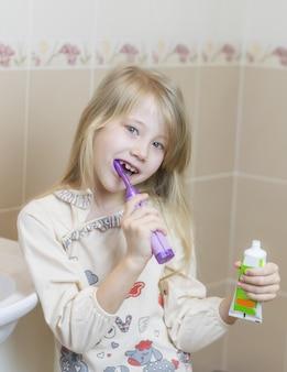 Vrolijk meisje die haar tanden in de badkamers nieuwe tandenborstel borstelen.