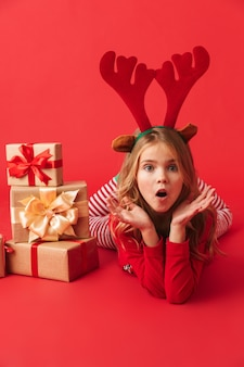 Vrolijk meisje die het kostuumzitting van kerstmis raindeer met geïsoleerde stapel giftdozen dragen