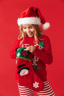 Vrolijk meisje draagt kerstkostuum staande geïsoleerd, cadeautjes nemen van een kerstsok