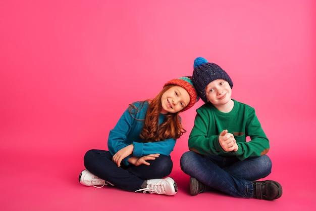 Vrolijk meisje en haar broer zittend op de vloer en glimlachen naar de camera