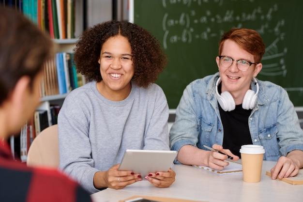 Vrolijk meisje en haar groupmate luisteren naar een van de jongens tijdens het bespreken van nieuwe creatieve ideeën in de klas