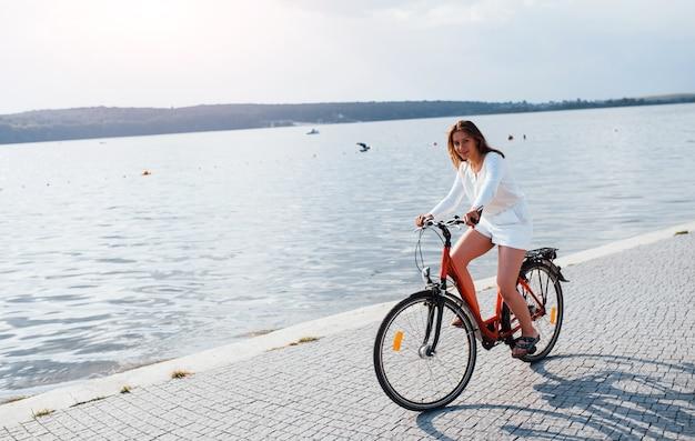 Vrolijk meisje fietst op het strand in de buurt van het meer op zonnige dag.