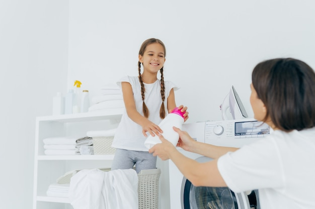 Vrolijk meisje geeft wasmiddel aan moeder, in wasruimte