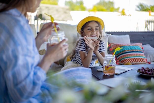 Vrolijk meisje genieten van ontbijt met moeder op buitenterras tijd samen doorbrengen spending
