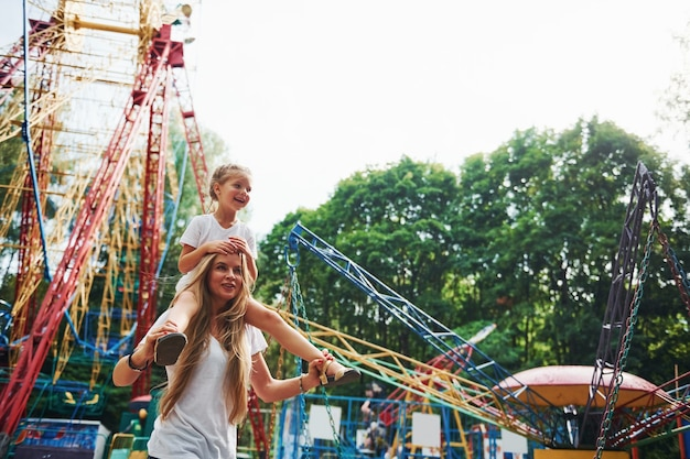 Vrolijk meisje haar moeder heeft een goede tijd samen in het park in de buurt van attracties.
