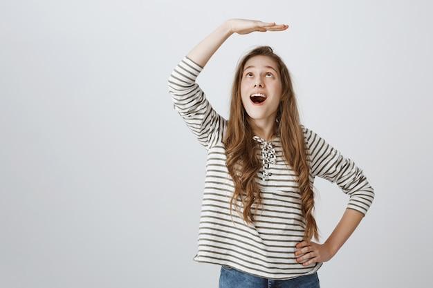 Vrolijk meisje hand opsteken boven het hoofd en verbaasd kijken