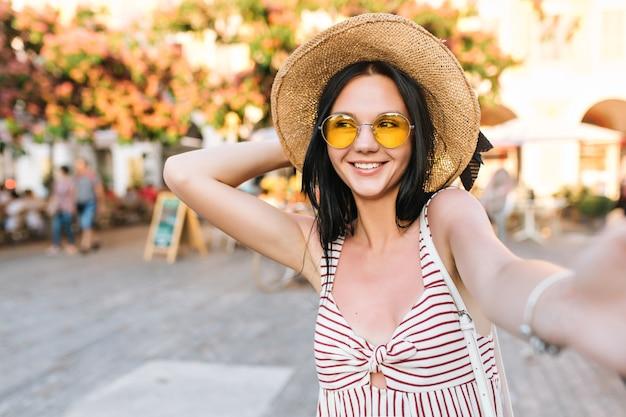 Vrolijk meisje hoed te houden tijdens het maken van selfie en wachten vrienden lachen op het stadsplein