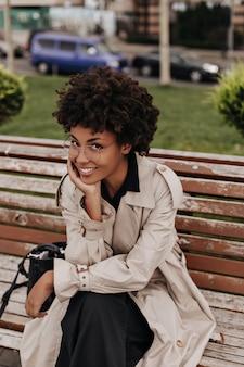 Vrolijk meisje in beige trenchcoat en bril glimlacht oprecht