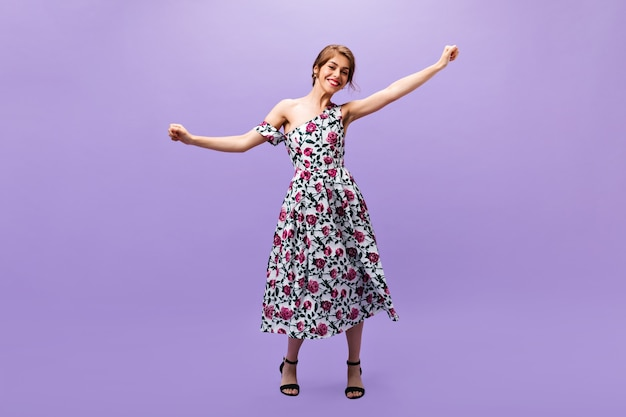 Vrolijk meisje in bloemenprint jurk dansen op paarse achtergrond. de mooie mooie jonge vrouw in modieuze zomeroutfit en zwarte hakken heeft ventilator.