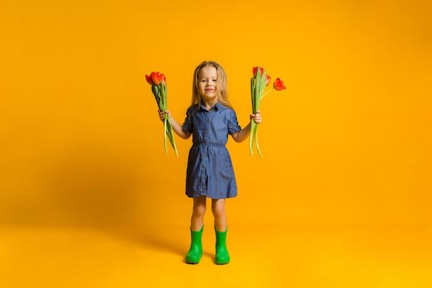 Vrolijk meisje in een blauwe jurk en groene rubberen laarzen staat met rode tulpen op een gele muur