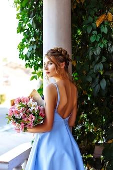Vrolijk meisje in een blauwe jurk met rode lippen en een stijlvol kapsel