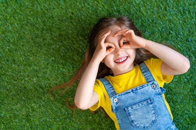 Vrolijk meisje in een denim jumpsuit, ligt op een groene weide