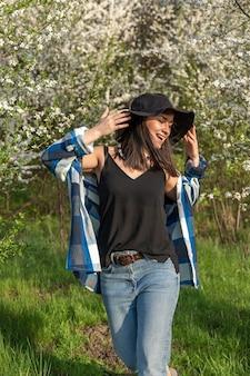 Vrolijk meisje in een hoed tussen de bloeiende bomen in de lente, in een casual stijl