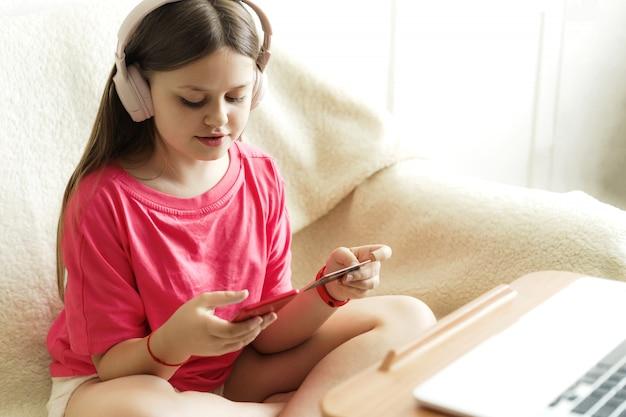 Vrolijk meisje in een koptelefoon en een roze t-shirt zit met een telefoon in haar hand en een creditcard