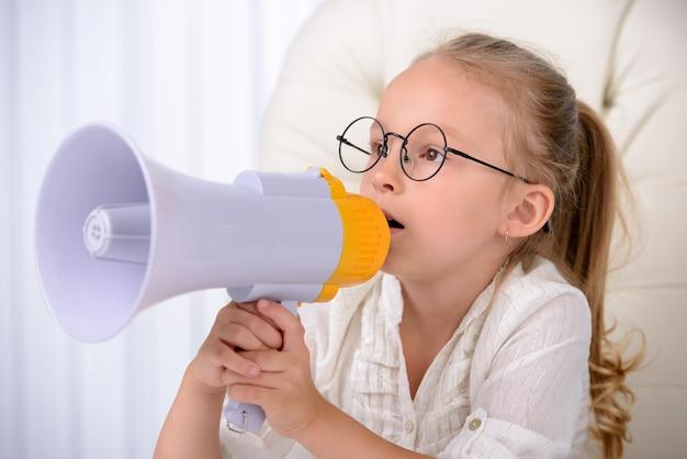 Vrolijk meisje in een plechtige schreeuw in megafoon.