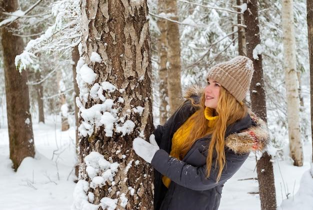 Vrolijk meisje in een warme trui en gebreide muts in een winterpark dat zich verschuilt achter een boomstam