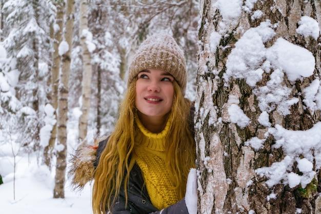 Vrolijk meisje in een winterpark lacht, gluurt van achter een boom