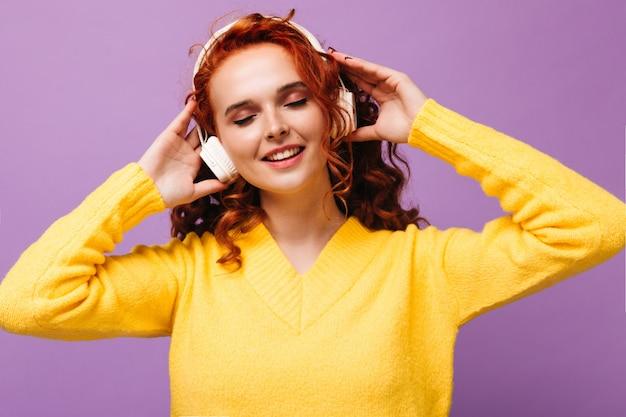 Vrolijk meisje in gele trui en koptelefoon luistert naar liedjes met een glimlach