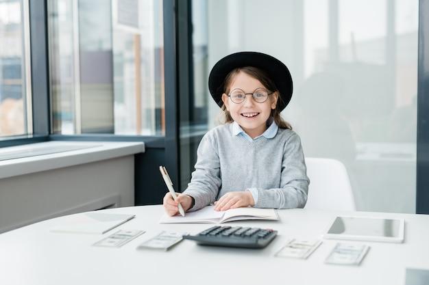 Vrolijk meisje in hoed en bril op zoek naar jou tijdens het tellen van geld en het maken van aantekeningen in beurt