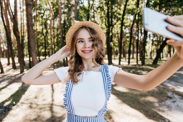 Vrolijk meisje in hoed met telefoon en poseren met verlegen glimlach. dromerige blanke dame die in het weekend in het bos aan het chillen is.