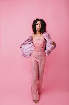 Vrolijk meisje in hoge geesten zingt en poseren in roze kamer. model met donkere huid en korte haarbewegingen.