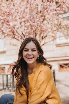 Vrolijk meisje in kasjmier trui lacht tegen de achtergrond van bloeiende sakura. portret van een vrouw in gele hoodie in de stad in het voorjaar