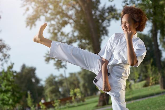 Vrolijk meisje in kimono die karate op straat beoefent