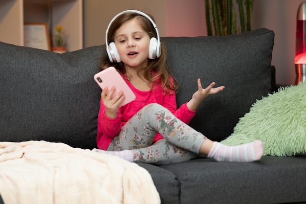 Vrolijk meisje in koptelefoon is dansen op de bank en het gebruik van smartphone scherm aan te raken. moderne technologie en gelukkig jeugdconcept