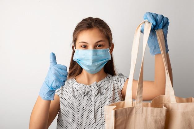 Vrolijk meisje in medische masker en beschermende handschoenen duimen opdagen, boodschappen doen, permanent met grote zak in de winkel