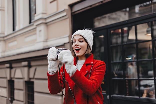 Vrolijk meisje in rood jasje, gebreide muts en wanten neemt foto van stad met retro camera.
