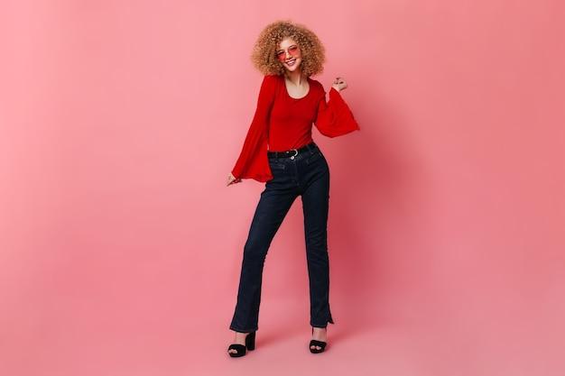 Vrolijk meisje in stijlvolle rode top en donkere denim broek dansen. portret van krullende dame in glazen op roze ruimte.