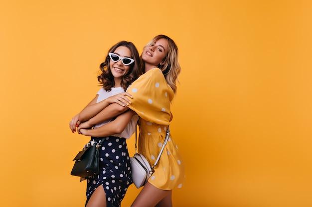 Vrolijk meisje in vintage witte zonnebril genieten van vrije tijd met vriend. betoverende, goedgeklede vrouwen die geel omhelzen.