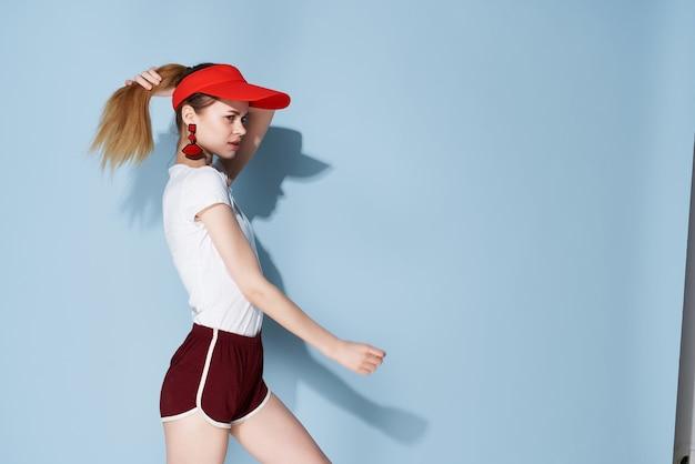 Vrolijk meisje in witte t-shirt en korte broek zomerkleren mode blauwe achtergrond