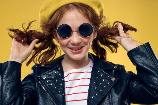Vrolijk meisje in zonnebril en hoed levensstijl studio gele mode als achtergrond. hoge kwaliteit foto