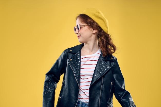 Vrolijk meisje in zonnebril en hoed levensstijl studio gele mode als achtergrond